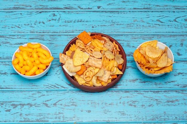 Aperitivos de cerveza como galletas, papas fritas, galletas en una superficie de madera