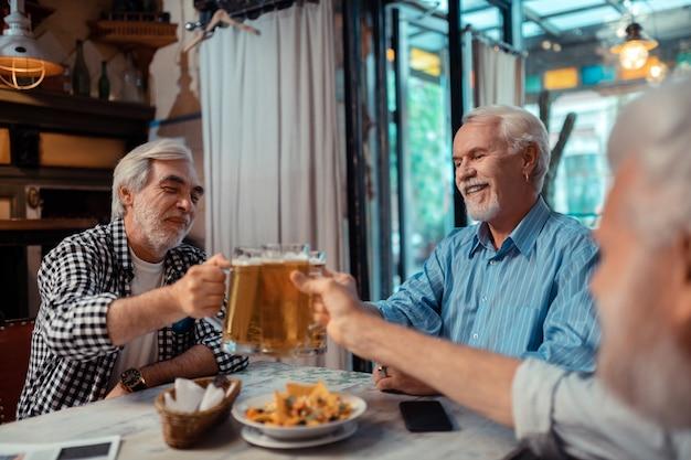Aperitivos y cerveza. hombres jubilados de pelo gris que se sienten aliviados mientras comen bocadillos y beben cerveza