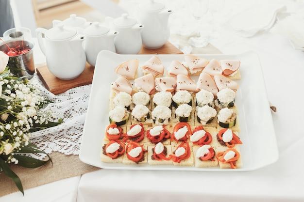 Aperitivos sabrosos de pescado y verduras servidos en plato cuadrado