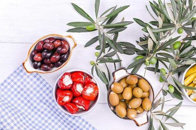 Aperitivos tradicionales, aceitunas de la cocina griega. fondo de madera blanca vista desde arriba. ramas frescas de aceitunas. copia espacio