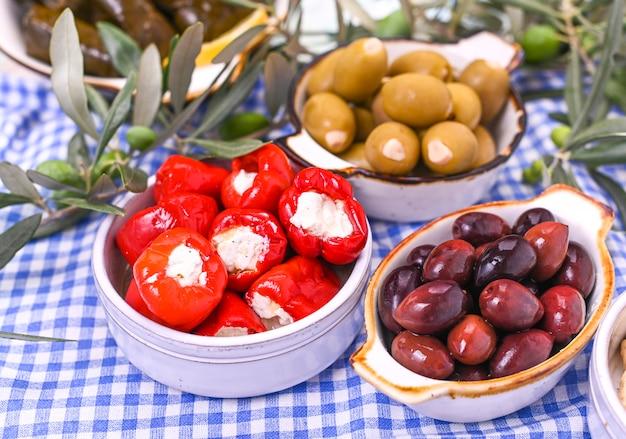 Aperitivos tradicionales, aceitunas verdes y rojas de la cocina griega. ramas frescas de aceitunas. copyspace encima. mantel a cuadros azul