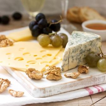 Aperitivos de varios tipos de queso, uvas, nueces y miel, servidos con vino blanco y tinto.