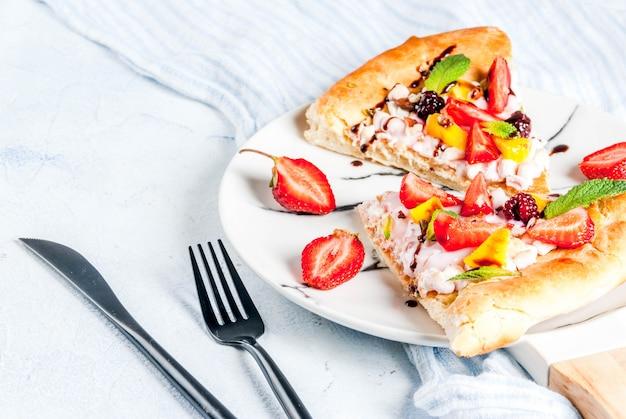 Aperitivos de verano. comida para fiesta. pizza de frutas con crema, grosellas, yogurt, fresas, mango, duraznos, plátanos, moras, chocolate, nueces, menta. en la mesa de color azul claro. copyspace