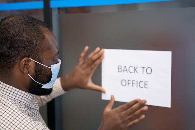 Apertura de oficina joven afroamericano en mascarilla protectora pegando letrero abierto con texto de nuevo a