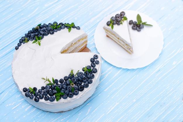 La apetitosa almohada de galletas de tarta de queso decorada con arándanos de crema blanca y menta se alza sobre una mesa rústica de madera azul. tarta dulce con pieza en plato
