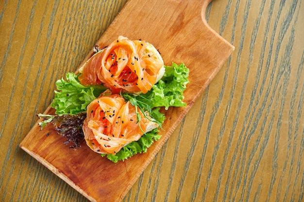 Apetitosa bruschetta con salmón y lechuga en una tabla de cortar en una pared de madera. primer plano, enfoque selectivo
