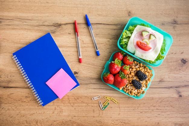 Apetitosa comida escolar y papelería sobre mesa.