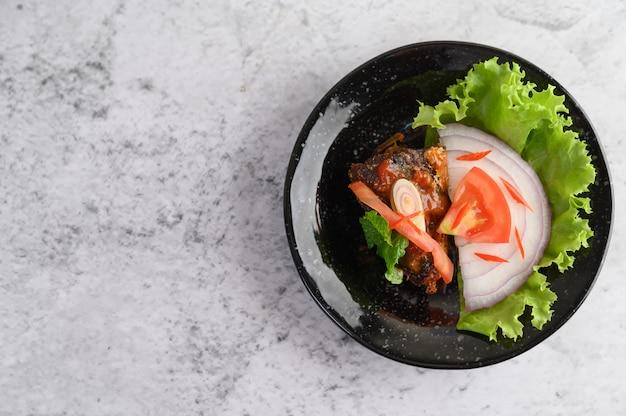 Apetitosa ensalada de sardina enlatada picante en salsa picante en un tazón de cerámica negra