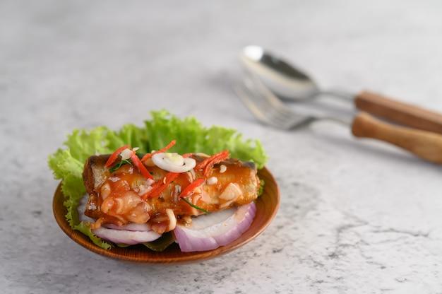 Apetitosa ensalada de sardina enlatada picante con salsa picante en un tazón de madera