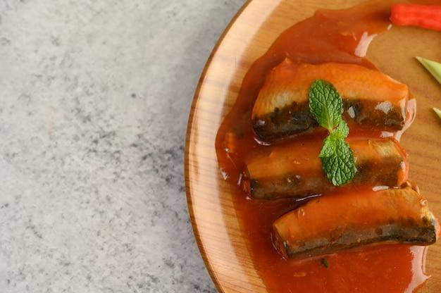 Apetitosa ensalada de sardina en salsa de tomate en bandeja de madera