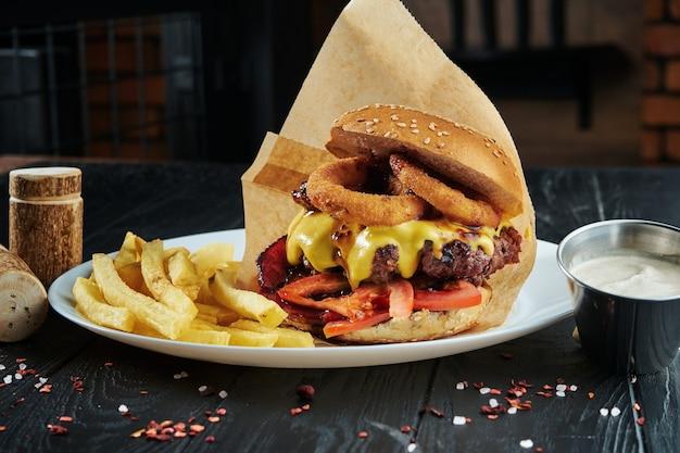 Apetitosa y jugosa hamburguesa con cebolla frita, queso derretido, tomate y chuleta de ternera en un plato blanco con papas fritas.