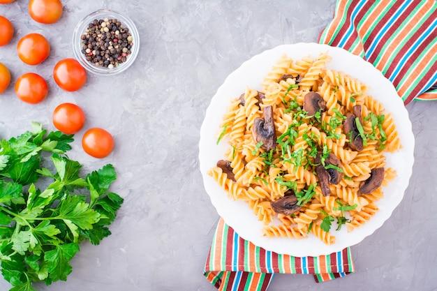 Apetitosa pasta con champiñones fritos y hierbas frescas en un plato, tomate y perejil sobre una mesa de hormigón, vista superior
