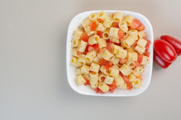 Apetitosa pasta penne con especias y rodajas de tomate en la placa blanca.