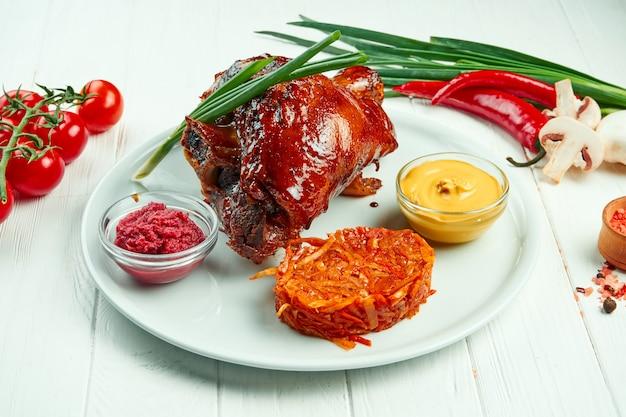 Apetitosa pierna de cerdo al horno en cerveza y miel con col frita y mostaza. merienda tradicional de cerveza alemana y checa.