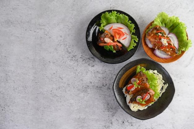 Apetitosa sardina enlatada picante en salsa picante en un tazón de cerámica negra