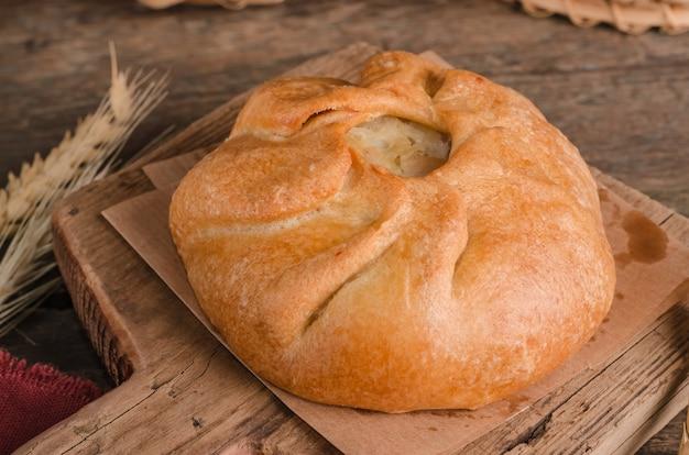 Apetitosa tarta rizada culinaria fresca con relleno sobre tabla de cortar de madera y fondo