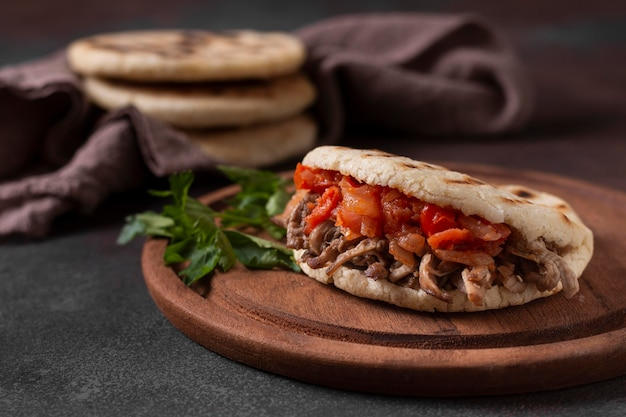Apetitosas arepas con carne y tomates