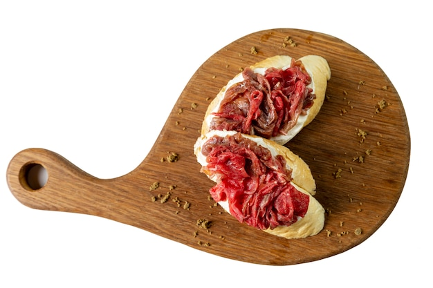 Apetitosas bruschettas con carne ahumada en una tabla de madera