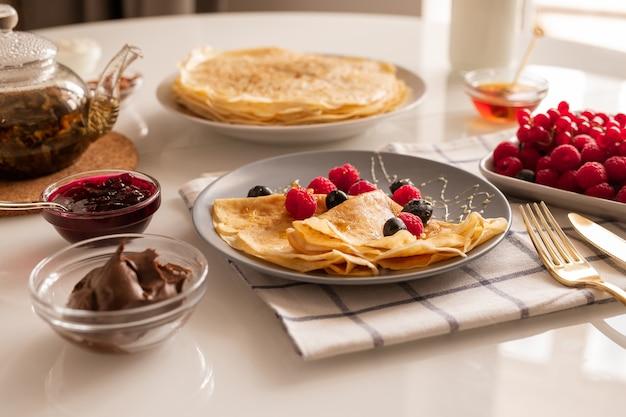 Apetitosas crepas caseras frescas con bayas y miel en un plato, cuencos con mermelada de cerezas y crema de chocolate, tetera y frambuesas maduras