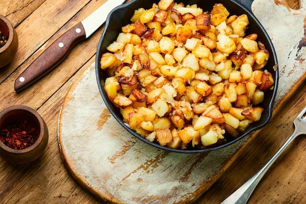 Apetitosas patatas fritas patatas asadas en la sartén de hierro fundido