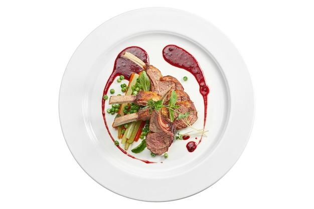 Apetitoso costillar de cordero a la plancha con verduras y salsa de frutos rojos en un plato blanco. aislado en superficie blanca. vista desde arriba