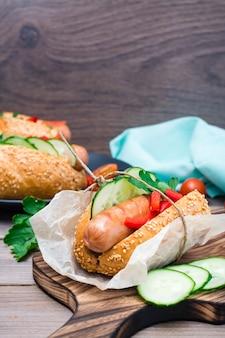Apetitoso hot dog hecho de salchichas fritas, panecillos y verduras frescas, envuelto en papel pergamino sobre una tabla para cortar sobre una mesa de madera