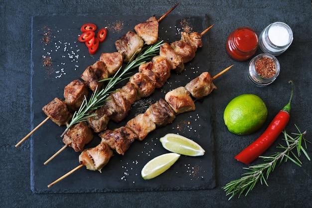 Apetitoso kebab con especias, chile y lima. brochetas de cerdo fragantes en un tablero de piedra.