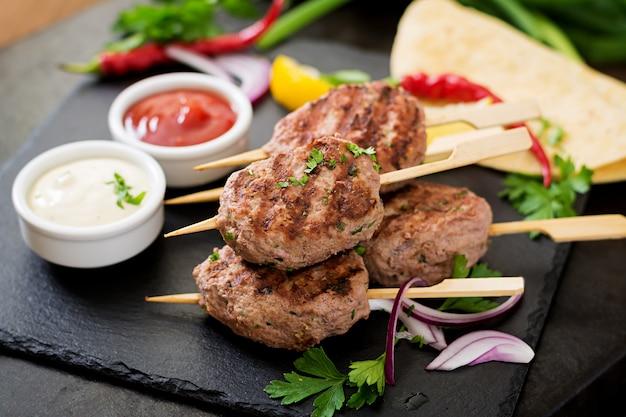 Apetitoso kofta kebab (albóndigas) con salsa y tacos de tortillas en mesa negra