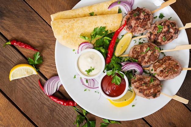Apetitoso kofta kebab (albóndigas) con salsa y tacos de tortillas en un plato blanco