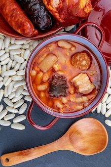 Apetitoso plato de cuchara. delicioso para otoño, invierno y todo el año. fabada asturiana, plato típico de asturias (españa). guiso de frijoles (alubias blancas) con chorizo, tocino, morcilla, tocino, ...