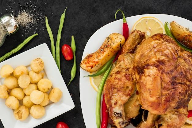 Apetitoso pollo entero a la plancha con diversas verduras.