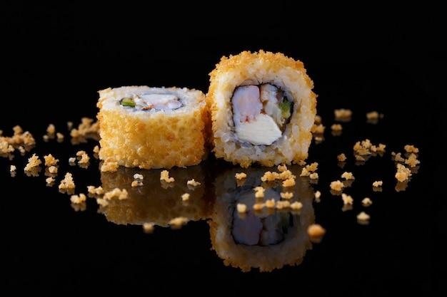 Apetitoso rollo de sushi al horno con pescado sobre un fondo negro con reflejo