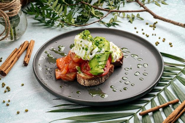 Apetitoso sándwich de aguacate con salmón y huevo escalfado para el desayuno
