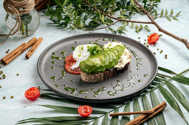 Apetitoso sándwich de aguacate con tomate y huevo escalfado para el desayuno