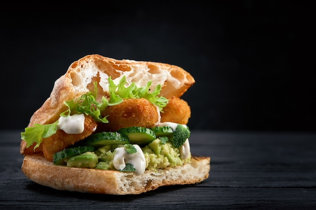 Apetitoso sandwich en una tabla de madera. sándwich de baguette con relleno de lechuga, rodajas de tomate. fondo de madera oscura vista desde arriba. de cerca. fotografía macro