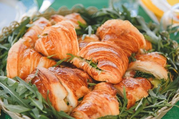 Apetitosos cruasanes con relleno de carne y queso y rúcula en una cesta rústica tejida.