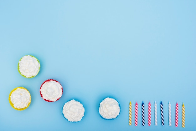 Apetitosos pasteles y velas sobre fondo azul