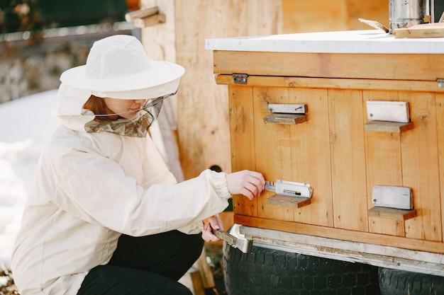 Apicultor de mujer cuida de las abejas. el uso de la mujer de la bata trabaja en el colmenar.