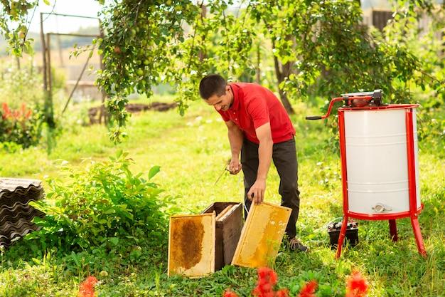 Un apicultor con una tapa protectora pone en funcionamiento un extractor de miel en la granja de abejas.