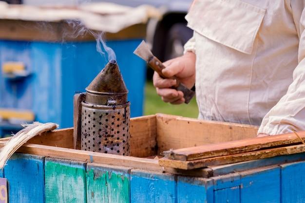 Apicultor trabajando con abejas y colmenas en colmenar. apicultor tirando marco de colmena.