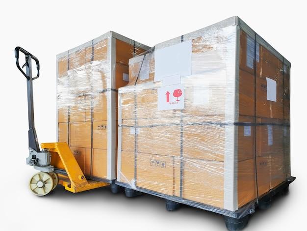 Apilado de cajas de cartón sobre palés de plástico y transpaleta manual aislado sobre un fondo blanco.