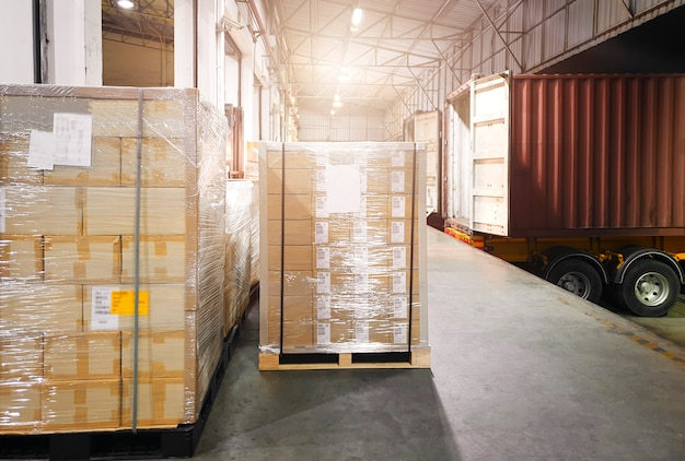Apilado de cajas de envío en paletas esperando para cargar en el camión contenedor.