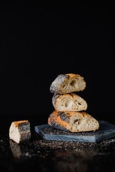 Apilado de rebanada de pan en pizarra roca contra el telón de fondo negro