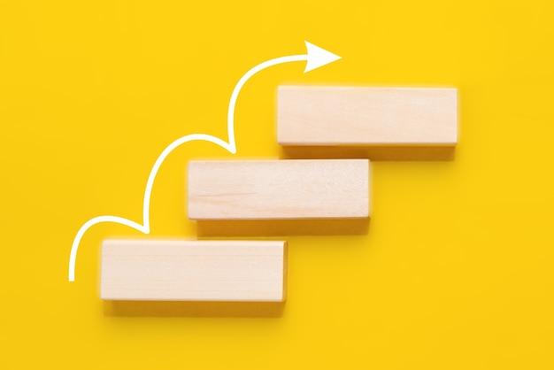 Apilamiento de bloques de madera como escalera con flecha blanca hacia arriba sobre fondo amarillo. escala de éxito en el concepto de crecimiento empresarial