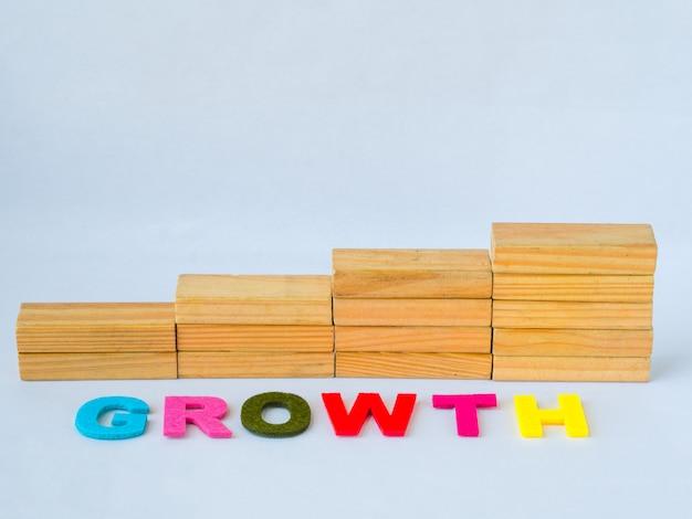 Apilamiento de bloques de madera como escalón con la palabra crecimiento