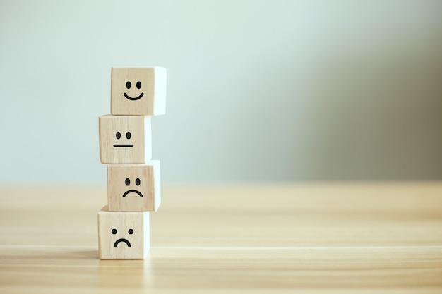 Apilamiento de cubos de madera con cara de emoción de icono y espacio de copia