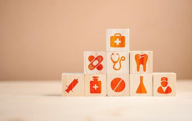 Apilamiento de cubos de madera de medicina sanitaria y el icono del hospital en la mesa.