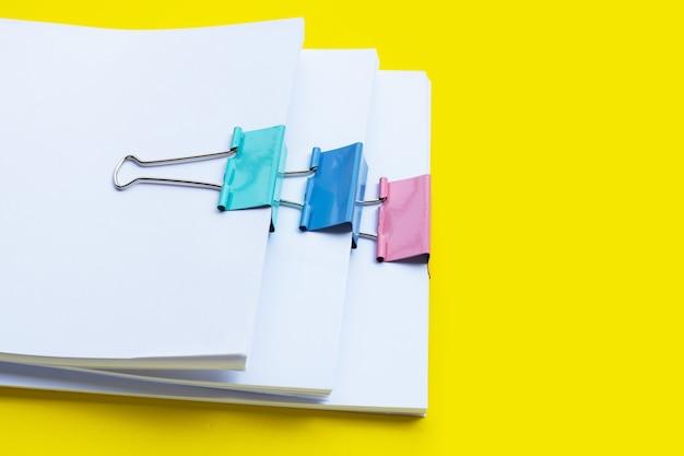 Apilamiento de documentos comerciales con clips de carpeta de colores sobre amarillo