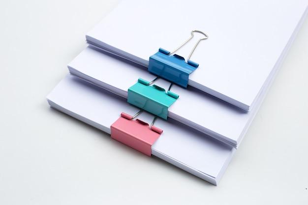 Apilamiento de documentos comerciales con clips de carpeta de colores sobre una superficie blanca