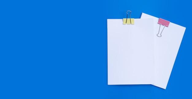 Apilamiento de documentos comerciales con coloridos clips de carpeta sobre superficie azul